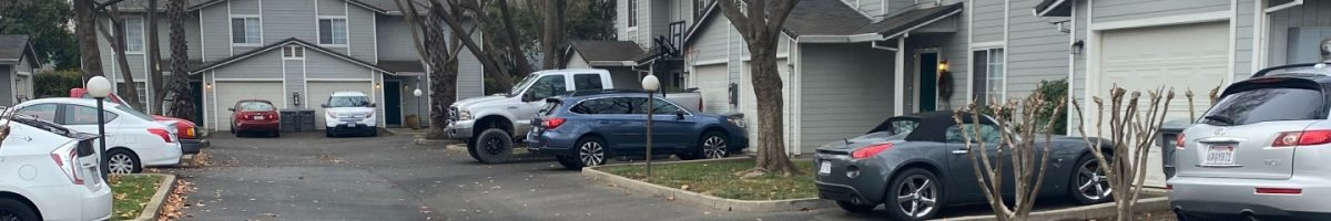 street view of gray houses with cars parked in driveway
