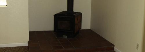 A black wood stove surrounded by tile