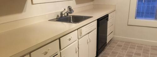 Kitchen shows white counterspace and metal sink.