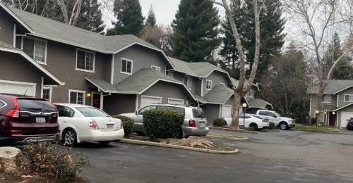 Several grey connected townhomes with cars parked in front.