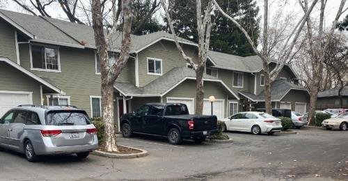 A wide view of the grey townhomes with several vehicles parked in front.